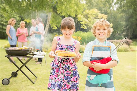 Brother and sister holding grilled corn near barbecue in backyard Stock Photo - Premium Royalty-Free, Code: 6113-07242362
