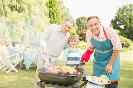 Multi-generation men grilling meat and corn at barbecue in backyard Stock Photo - Premium Royalty-Free, Code: 6113-07242370