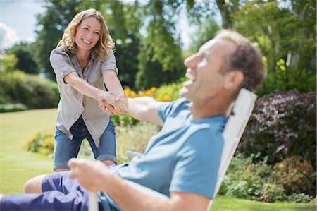 Woman pulling boyfriend out of chair in backyard Stock Photo - Premium Royalty-Free, Code: 6113-07242377