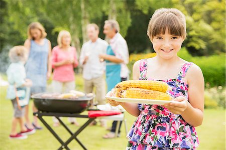 Smiling girl holding grilled corn in backyard Stock Photo - Premium Royalty-Free, Code: 6113-07242374