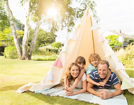 Family relaxing in teepee in backyard Stock Photo - Premium Royalty-Free, Code: 6113-07242388