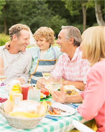 Family enjoying lunch at table in backyard Stock Photo - Premium Royalty-Free, Code: 6113-07242389