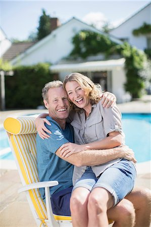 Couple sitting in lounge chair at poolside Stock Photo - Premium Royalty-Free, Code: 6113-07242393
