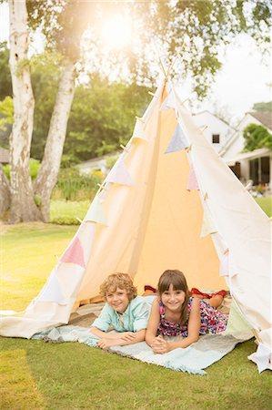 Children laying in teepee in backyard Stock Photo - Premium Royalty-Free, Code: 6113-07242390