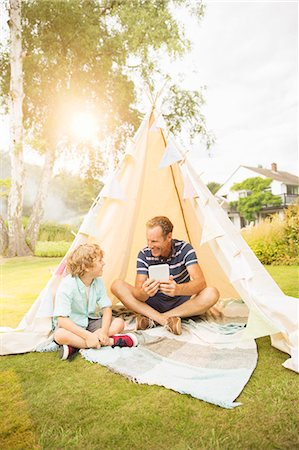 family  fun  outside - Father and son using digital tablet in teepee in backyard Stock Photo - Premium Royalty-Free, Code: 6113-07242392