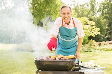 Man grilling food on barbecue in backyard Stock Photo - Premium Royalty-Free, Code: 6113-07242397
