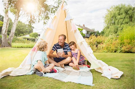 Father and children relaxing in teepee in backyard Stock Photo - Premium Royalty-Free, Code: 6113-07242394