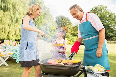 Multi-generation family standing at barbecue in backyard Stock Photo - Premium Royalty-Free, Code: 6113-07242395