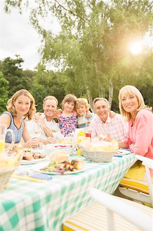 Multi-generation family eating lunch at table in backyard Stock Photo - Premium Royalty-Free, Code: 6113-07242303