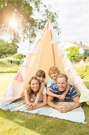Family relaxing in teepee in backyard Stock Photo - Premium Royalty-Free, Code: 6113-07242301