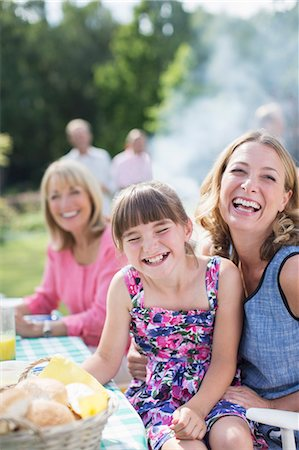 Mother and daughter laughing at table in backyard Stock Photo - Premium Royalty-Free, Code: 6113-07242309
