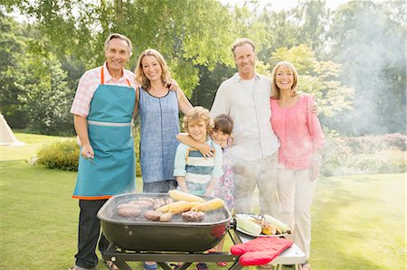 Multi-generation family standing at barbecue in backyard Stock Photo - Premium Royalty-Free, Code: 6113-07242313