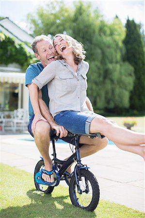Couple riding small bicycle in grass Stock Photo - Premium Royalty-Free, Code: 6113-07242328