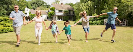 Multi-generation family holding hands and running in grass Stock Photo - Premium Royalty-Free, Code: 6113-07242333