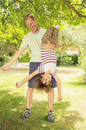 dangling - Father holding son upside-down in backyard Stock Photo - Premium Royalty-Free, Code: 6113-07242339