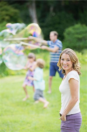 Family playing with bubbles in backyard Stock Photo - Premium Royalty-Free, Code: 6113-07242445