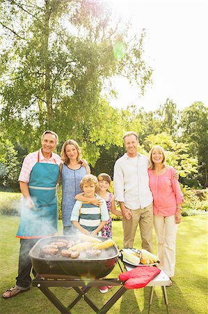 Multi-generation family standing at barbecue in backyard Stock Photo - Premium Royalty-Free, Code: 6113-07242400