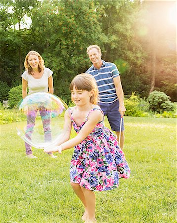 Family playing with bubbles in backyard Stock Photo - Premium Royalty-Free, Code: 6113-07242406