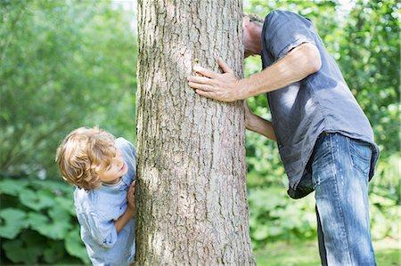Father and son peeking around tree Stock Photo - Premium Royalty-Free, Code: 6113-07242409