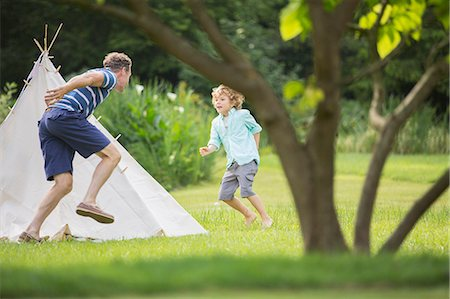 Father chasing son around teepee in backyard Stock Photo - Premium Royalty-Free, Code: 6113-07242428