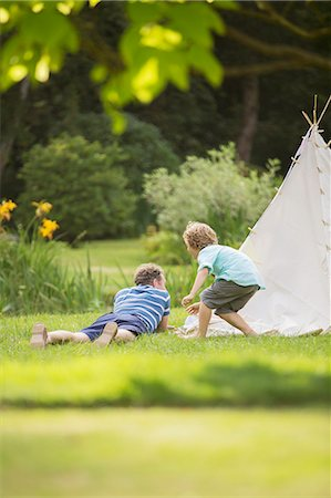 Father and son laying outside teepee Stock Photo - Premium Royalty-Free, Code: 6113-07242434