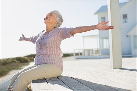 Senior woman with arms outstretched on sunny deck Stock Photo - Premium Royalty-Free, Code: 6113-07242556