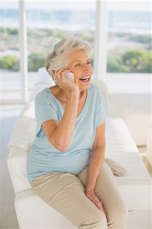 Senior woman talking on cell phone in living room Stock Photo - Premium Royalty-Free, Code: 6113-07242563