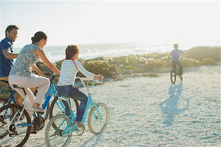 preteen beach - Family riding bicycles on sunny beach Stock Photo - Premium Royalty-Free, Code: 6113-07242565