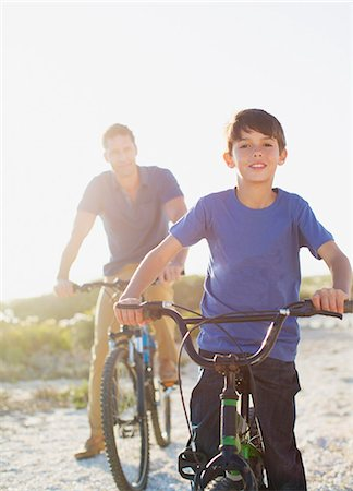 preteen beach - Father and son riding bicycles on sunny beach Stock Photo - Premium Royalty-Free, Code: 6113-07242572