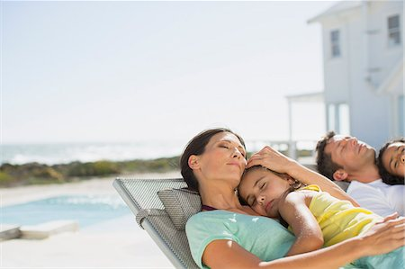 Family sleeping in lounge chairs at poolside Stock Photo - Premium Royalty-Free, Code: 6113-07242507