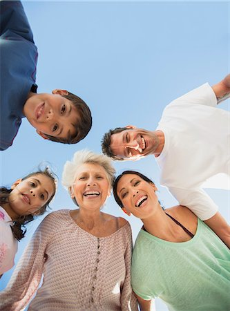 Multi-generation family smiling in huddle against blue sky Stock Photo - Premium Royalty-Free, Code: 6113-07242509