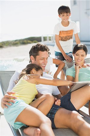 preteen touch - Family using digital tablet on lounge chairs at poolside Stock Photo - Premium Royalty-Free, Code: 6113-07242511