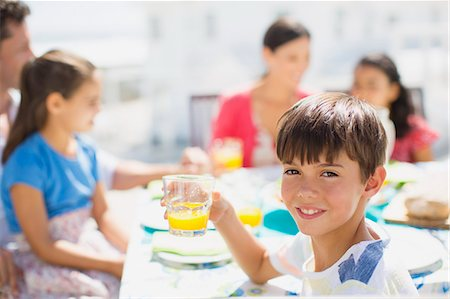 Boy drinking juice at table on sunny patio Stock Photo - Premium Royalty-Free, Code: 6113-07242514