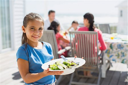 people eating at lunch - Girl holding salad on sunny patio Stock Photo - Premium Royalty-Free, Code: 6113-07242524
