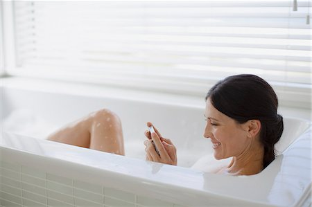 Woman using cell phone in bubble bath Stock Photo - Premium Royalty-Free, Code: 6113-07242647