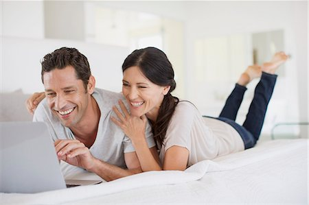 Couple using laptop on bed Stock Photo - Premium Royalty-Free, Code: 6113-07242652