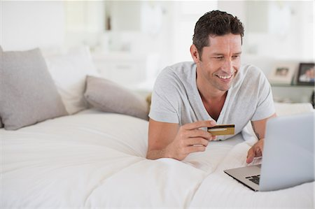 ebusiness - Man shopping online with laptop on bed Stock Photo - Premium Royalty-Free, Code: 6113-07242654