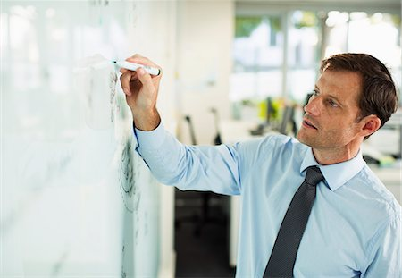 strategy - Businessman writing on whiteboard in office Stock Photo - Premium Royalty-Free, Code: 6113-07242689