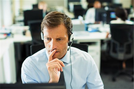 services - Businessman wearing headset in office Stock Photo - Premium Royalty-Free, Code: 6113-07242692