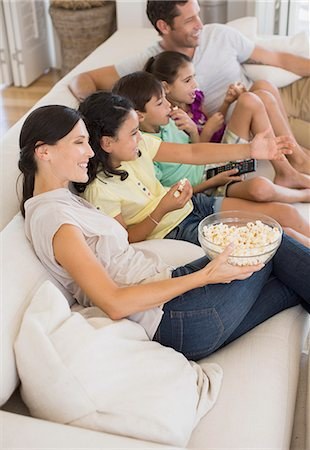 Family watching movie on sofa in living room Stock Photo - Premium Royalty-Free, Code: 6113-07242607