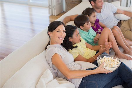 Family watching movie on sofa in living room Stock Photo - Premium Royalty-Free, Code: 6113-07242604