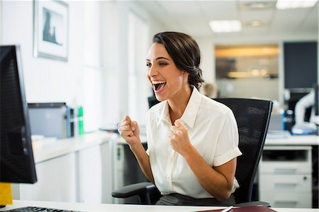 Businesswoman cheering in office Stock Photo - Premium Royalty-Free, Code: 6113-07242741