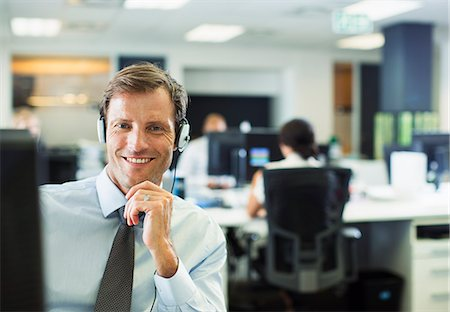 Businessman wearing headset in office Stock Photo - Premium Royalty-Free, Code: 6113-07242742
