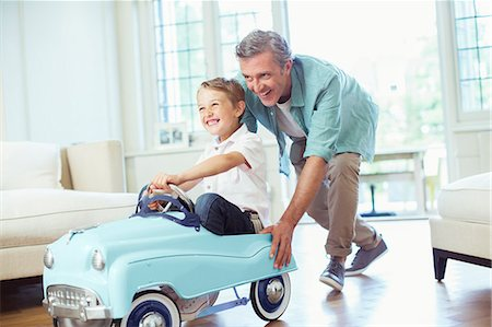 Father pushing son in toy car Stock Photo - Premium Royalty-Free, Code: 6113-07242785