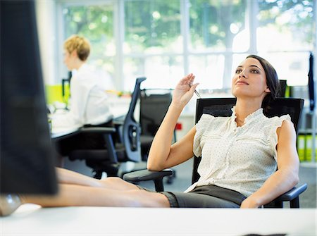 Businesswoman relaxing with feet up on desk in office Stock Photo - Premium Royalty-Free, Code: 6113-07242733