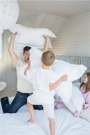 preteen boys playing - Father and children having pillow fight Stock Photo - Premium Royalty-Free, Code: 6113-07242857