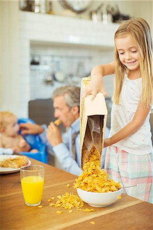 Girl pouring bowl cereal on breakfast table Stock Photo - Premium Royalty-Free, Code: 6113-07242869