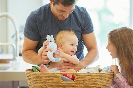 Father and children sorting laundry Stock Photo - Premium Royalty-Free, Code: 6113-07242870