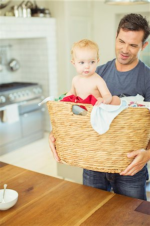 Father carrying baby in laundry basket Stock Photo - Premium Royalty-Free, Code: 6113-07242876