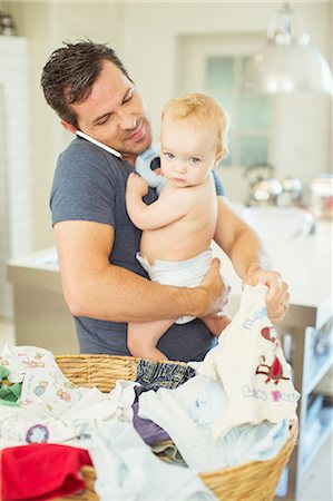 Father holding baby and folding laundry while talking on cell phone Stock Photo - Premium Royalty-Free, Code: 6113-07242878